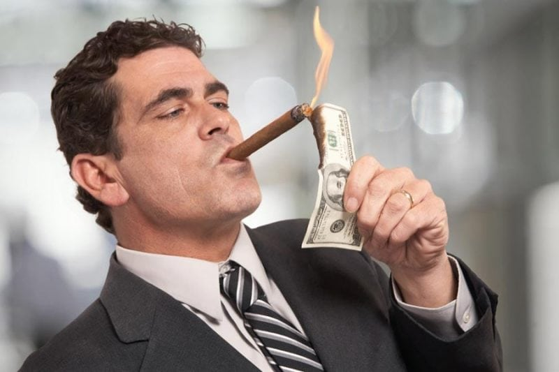 picture of a guy burning money